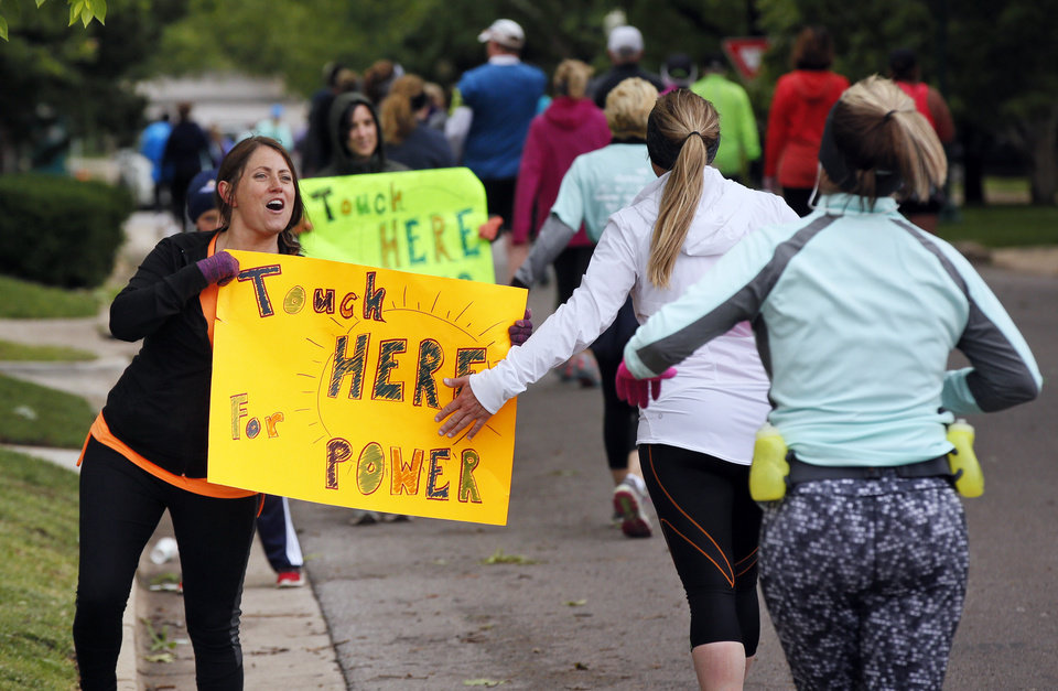 Photo - Tammy Streeter, left, cheers on runners at NW 14 and Shartel Ave. during the Oklahoma City Memorial Marathon in Oklahoma City, Sunday, April 30, 2017. Photo by Nate Billings, The Oklahoman