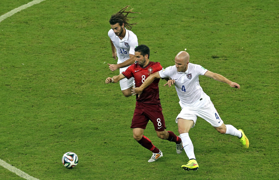 Photo - Portugal's Joao Moutinho is challenged by United States' Michael Bradley, right, and Kyle Beckerman, left, during the group G World Cup soccer match between the USA and Portugal at the Arena da Amazonia in Manaus, Brazil, Sunday, June 22, 2014. (AP Photo/Themba Hadebe)