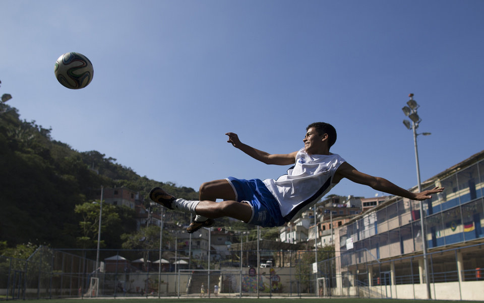 Photo - In this June 17, 2014 photo, Andre Rodrigues de Principe, 14, known as Andrezinho to his neighbors, kicks the ball during his practice session in the Vidigal slum of Rio de Janeiro, Brazil. Although he's trained with two of Brazil's premier teams, Fluminense and Vasco da Gama, he's currently only playing for his local squad comprised of other kids from his Vidigal favela, as slums here are known. (AP Photo/Leo Correa)