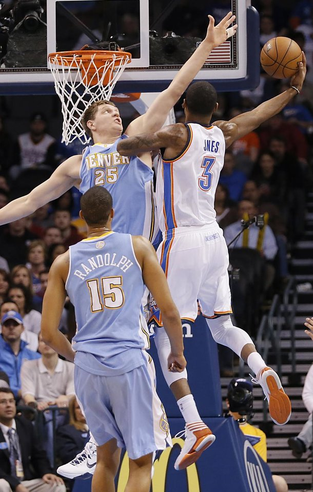 Photo - Oklahoma City's Perry Jones (3) drives past Denver's Timofey Mozgov (25) during the NBA basketball game between the Oklahoma City Thunder and the Denver Nuggets at the Chesapeake Energy Arena on Wednesday, Jan. 16, 2013, in Oklahoma City, Okla.  Photo by Chris Landsberger, The Oklahoman