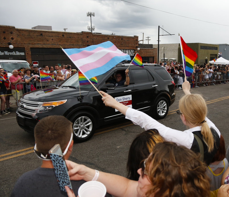 Photo - A spectator waves flags to a participant at the OKC Pride Parade on NW 39  in Oklahoma City, Sunday, June 26, 2016. Photo by Kurt Steiss, The Oklahoman