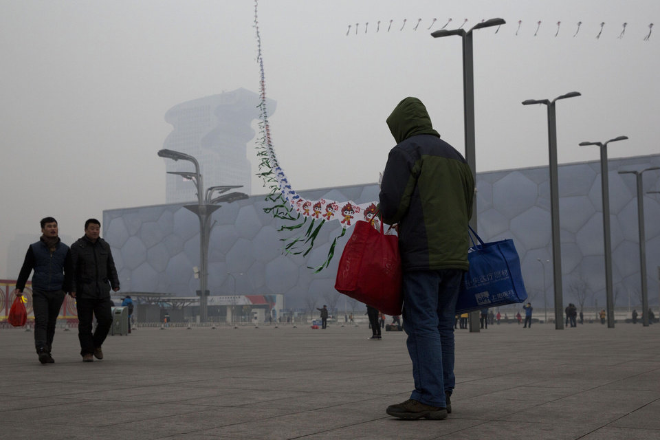 Photo - In this picture taken Sunday, Feb. 23, 2014, a street vendor flies kites printed with the Beijing Olympic games mascot image near the Water Cube aquatic center in Beijing, China. The Water Cube _ where U.S. swimmer Michael Phelps made history by winning eight gold medals _ has been transformed into a water park popular among local families. Its operators even peddle purified glacier water under the Water Cube brand for additional income. Beijing, which spent more than $2 billion to build 31 venues for the 2008 Summer Games, is reaping some income and tourism benefits from two flagship venues, though many sites need government subsidies to meet hefty operation and maintenance costs. (AP Photo/Ng Han Guan)