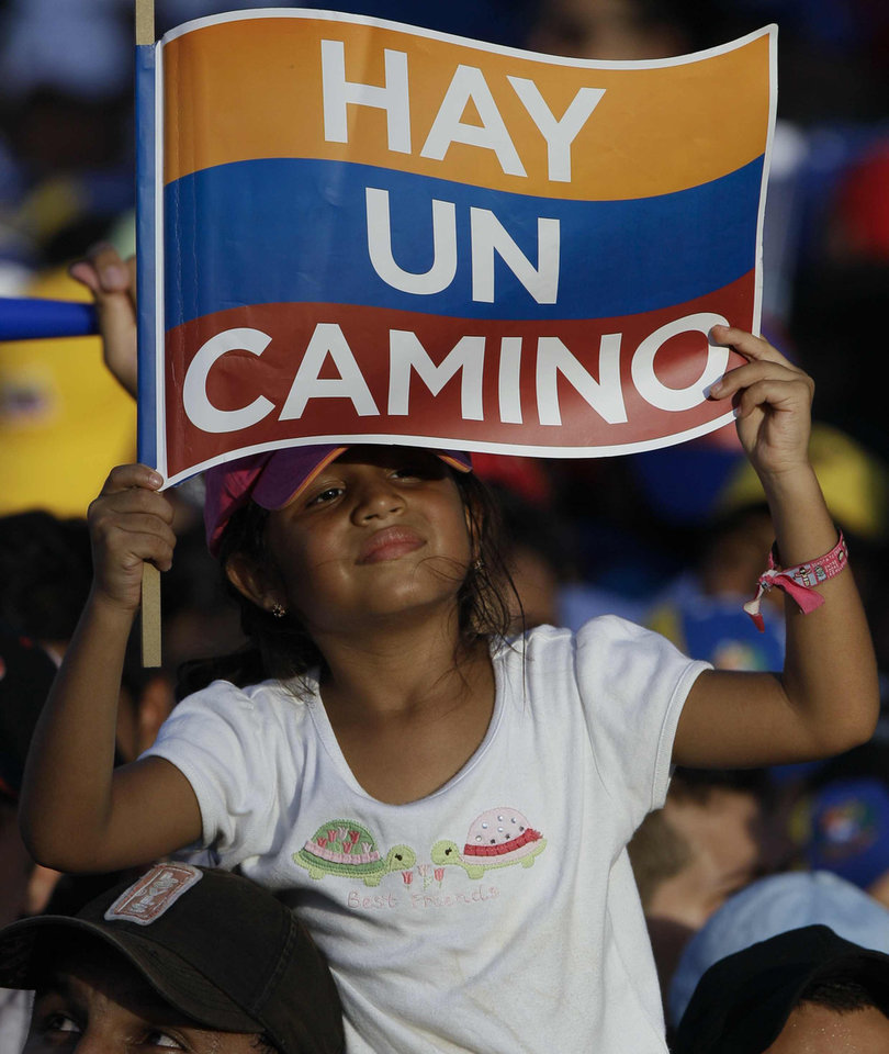 "A supporter of opposition presidential candidate Henrique Capriles holds up a sign with the colors of the Venezuelan flag that reads in Spanish ""There is a way"" during his closing campaign rally in Barquisimeto, Venezuela, Thursday, Oct. 4, 2012. Capriles will run against President Hugo Chavez in the presidential elections Oct. 7. (AP Photo/Fernando Llano)"