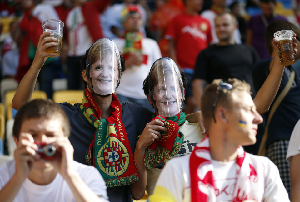<p>Portuguese fans wearing masks of German Chancellor Angela Merkel hold glasses of beer on the stands during the Euro 2012 soccer championship Group B match between Denmark and Portugal in Lviv, Ukraine, Wednesday, June 13, 2012. (AP Photo/Armando Franca)</p>
