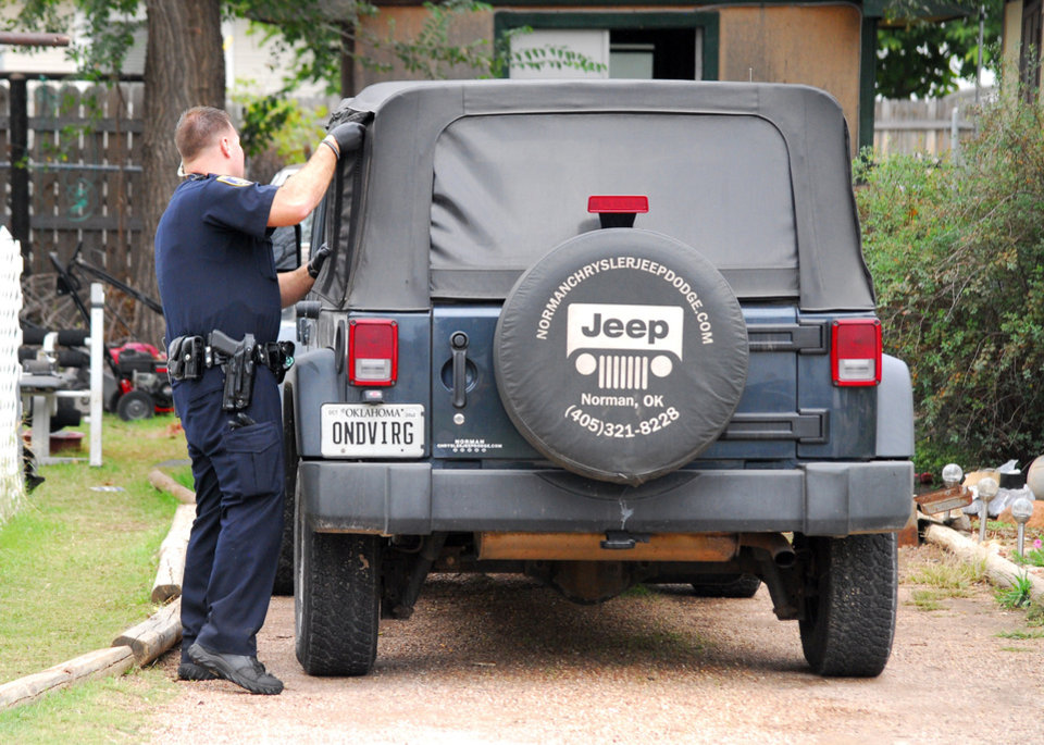 A Norman police officer searches a Jeep in front of house at 207 E Johnson St. on Wednesday afternoon. Police executed a search warrant on the house in connection with a shooting that happened near the residence Tuesday night. <strong>Andrew Knittle - Andrew Knittle</strong>
