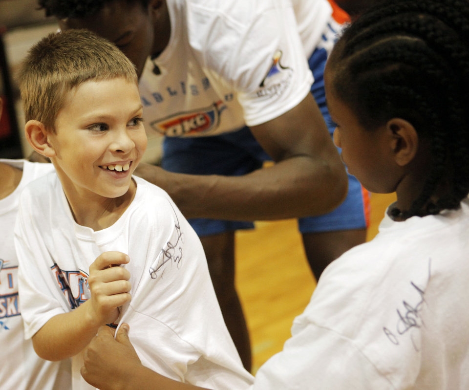 Photo - Aidan White, 9 of Midwest City (left), shows off his freshly autographed shirt by Oklahoma City Thunder center Hasheem Thabeet to Demetrius Wilburn, 8 of California, at the Thunder basketball camp at Carl Albert High School in Midwest City on June 25, 2013. Photo by KT KING, The Oklahoman