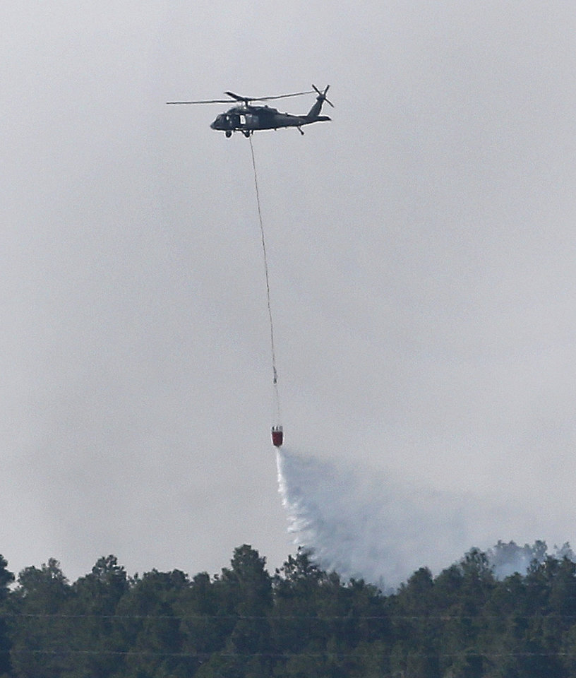 Photo - A U.S. Army Huey helicopter makes a water drop on a wildfire in the Black Forest area north of Colorado Springs, Colo., on Wednesday, June 12, 2013.  Authorities initially estimated that between 40 and 60 houses were destroyed in Black Forest, a heavily wooded residential area northeast of Colorado Springs, but they are still surveying the damage. AP Photo/Ed Andrieski)
