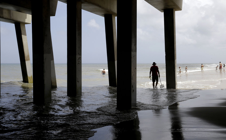 Photo - Tourists enjoy a calm ocean in Nags Head, N.C., Thursday, July 3, 2014. Hurricane Arthur is forecast to pass by Hatteras Island on Friday morning. The island is under mandatory evacuation orders. (AP Photo/Gerry Broome)