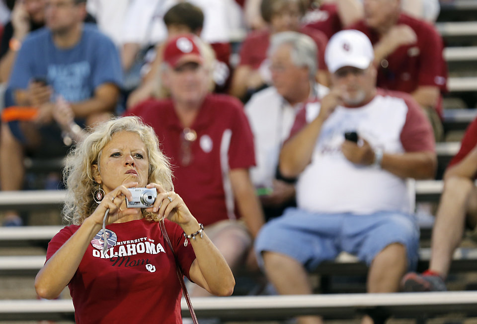 Photo - A Sooner fan looks for just the right photo during the college football game between the University of Oklahoma Sooners (OU) and the University of Texas El Paso Miners (UTEP) at Sun Bowl Stadium on Saturday, Sept. 1, 2012, in El Paso, Tex.  Photo by Chris Landsberger, The Oklahoman