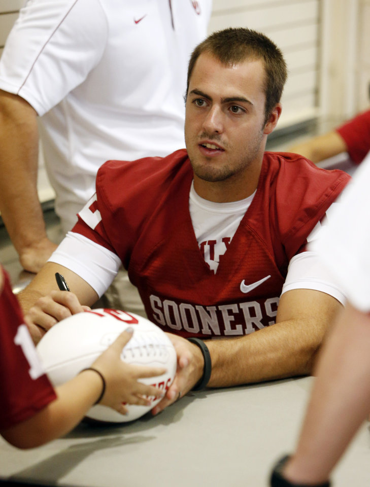 Photo - Quarterback Landry Jones signs autographs during the Meet the Sooners event inside Gaylord Family/Oklahoma Memorial Stadium at the University of Oklahoma on Saturday, Aug. 4, 2012, in Norman, Okla.  Photo by Steve Sisney, The Oklahoman