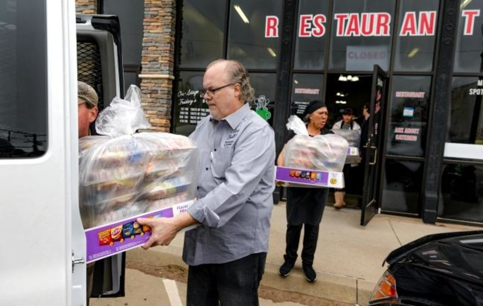 Photo - Wayne and Donna Heins carry out the 200 lunches that Clara Belle's restaurant catered for the staff at Mabel Bassett in McLoud, Okla. on Friday, April 3, 2020. Prison volunteers raised money to pay for lunch boxes for staff at the prison.  [Chris Landsberger/The Oklahoman]