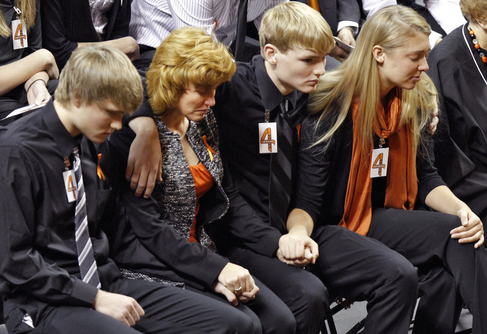 Photo - Alex Budke, left, sits next to his mother Shelley, brother Brett and daughter Sara during the memorial service for Oklahoma State head basketball coach Kurt Budke and assistant coach Miranda Serna at Gallagher-Iba Arena on Monday, Nov. 21, 2011 in Stillwater, Okla. The two were killed in a plane crash along with former state senator Olin Branstetter and his wife Paula while on a recruiting trip in central Arkansas last Thursday. Photo by Chris Landsberger, The Oklahoman