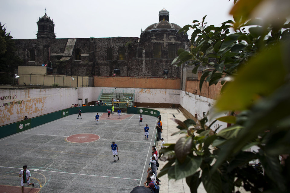 Photo - In this Sunday, June 8, 2014 photo, Cruz Azul and Paris teams compete for third place during the 2014 finals of the Ignacio Trigueros Soccer League for the Blind and Visually Impaired, in Mexico City. The league plays a version of indoor soccer, with six people a side playing on a hard outdoor court surrounded by boards. (AP Photo/Rebecca Blackwell)