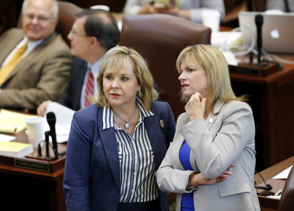 Photo -  Gov. Mary Fallin, left, and Rep. Leslie Osborn discuss the tally as lawmakers cast their votes on the cigarette tax measure. Osborn chairs the House Appropriations and Budget Committee. House members were unable to get enough votes to raise the cigarette tax rate after a lengthy vote on Monday. [Photo by Jim Beckel, The Oklahoman]