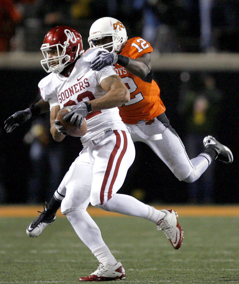 Photo - Oklahoma's James Hanna (82) makes a catch as Oklahoma State's Johnny Thomas (12) tries to bring him down during the Bedlam college football game between the University of Oklahoma Sooners (OU) and the Oklahoma State University Cowboys (OSU) at Boone Pickens Stadium in Stillwater, Okla., Saturday, Nov. 27, 2010. Photo by Sarah Phipps, The Oklahoman