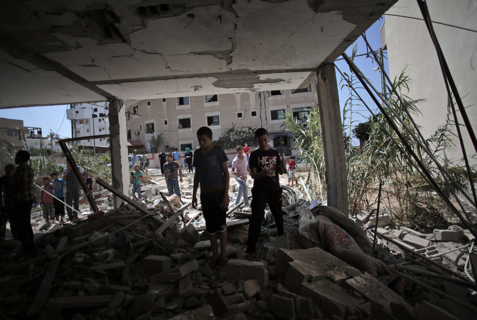 Photo - Palestinians inspect the rubble of a destroyed house following an Israeli strike killing Christian woman Jalila Ayyad, 70, in Gaza City on Sunday, July 27, 2014. (AP Photo/Khalil Hamra)