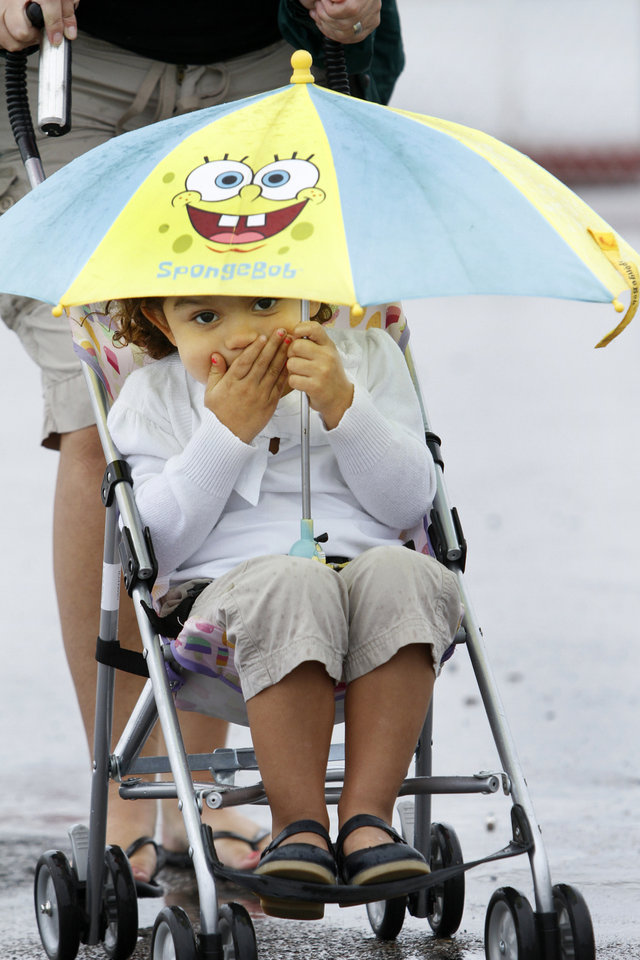 Photo - Brooks Beavers, 3, keeps dry under her umbrella as her aunt Brook Beavers pushes her during the opening day of the Oklahoma State Fair at State Fair Park in Oklahoma City, Thursday  September  13, 2012. Photo By Steve Gooch, The Oklahoman