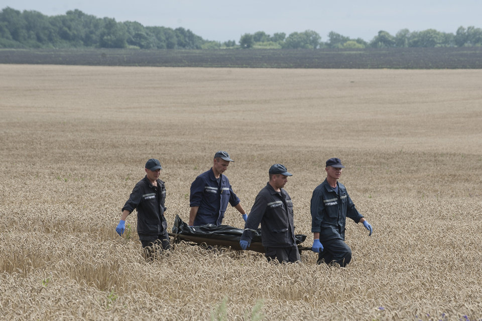 Photo - Emergency workers carry a stretcher with a victim's body in a bag at the crash site of a Malaysia Airlines jet near the village of Hrabove, eastern Ukraine, Saturday, July 19, 2014. Ukraine accused Russia on Saturday of helping separatist rebels destroy evidence at the crash site of a Malaysia Airlines plane shot down in rebel-held territory — a charge the rebels denied. (AP Photo/Evgeniy Maloletka)