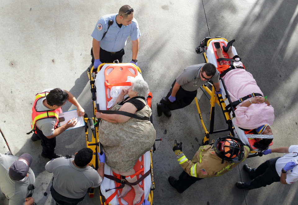 Emergency personnel attend to injured passengers after a bus accident at Miami International Airport on Saturday, Dec. 1, 2012 in Miami. Officials say a bus has hit an overpass, killing at least one person and injuring more than two-dozen people on board. Airport spokesman Greg Chin says the large, white bus hit the overpass going into the airport\'s arrivals section on Saturday morning. The bus was going about 20 mph when it clipped the roof entrance. (AP Photo/El Nuevo Herald, Roberto Koltun)