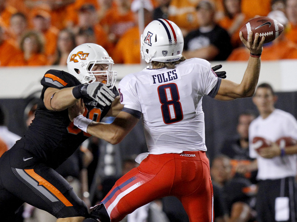 Oklahoma State's Cooper Bassett (80) puts pressure on Arizona's Nick Foles (8) during their game Thursday in Stillwater. PHOTO BY BRYAN TERRY, The Oklahoman