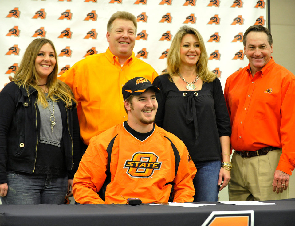 Photo - Aledo High Scool lineman Michael Wilson, center,  with sister Stephanie, father Mike, mom Becky, mom and Aledo football coach Tim Buchanan smile as Wilson signs a national letter of intent to attend the Oklahoma State and play football during a national signing day event, Wednesday, Feb. 1, 2012, in Aledo, Texas.   (AP Photo/The Fort Worth Star-Telegram, Max Faulkner) MAGS OUT ORG XMIT: TXFOR204