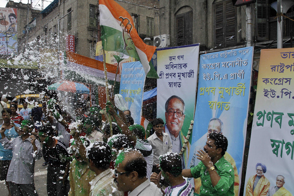 Photo -   Activists of India's ruling Congress party celebrate the victory of Pranab Mukherjee, his portrait seen, center, in India's presidential election in Kolkata, India, Sunday, July 22, 2012. Former Finance Minister Pranab Mukherjee, the candidate from India's governing Congress party, has claimed victory in the election for the country's next president, a largely ceremonial position. His rival, Purno Agitok Sangma, conceded defeat. (AP Photo/Bikas Das)