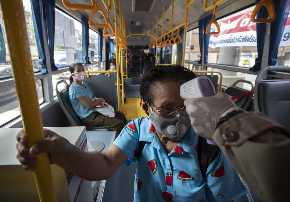 Photo -  An officer checks the temperature of a passenger in a bus at a health checkpoint in Bangkok, Thailand, Friday, April 3, 2020. Thailand's prime minister announced a nationwide 10 p.m.-to-4 a.m curfew starting Friday to combat the spread of the coronavirus. The new coronavirus causes mild or moderate symptoms for most people, but for some, especially older adults and people with existing health problems, it can cause more severe illness or death. (AP Photo/Sakchai Lalit)