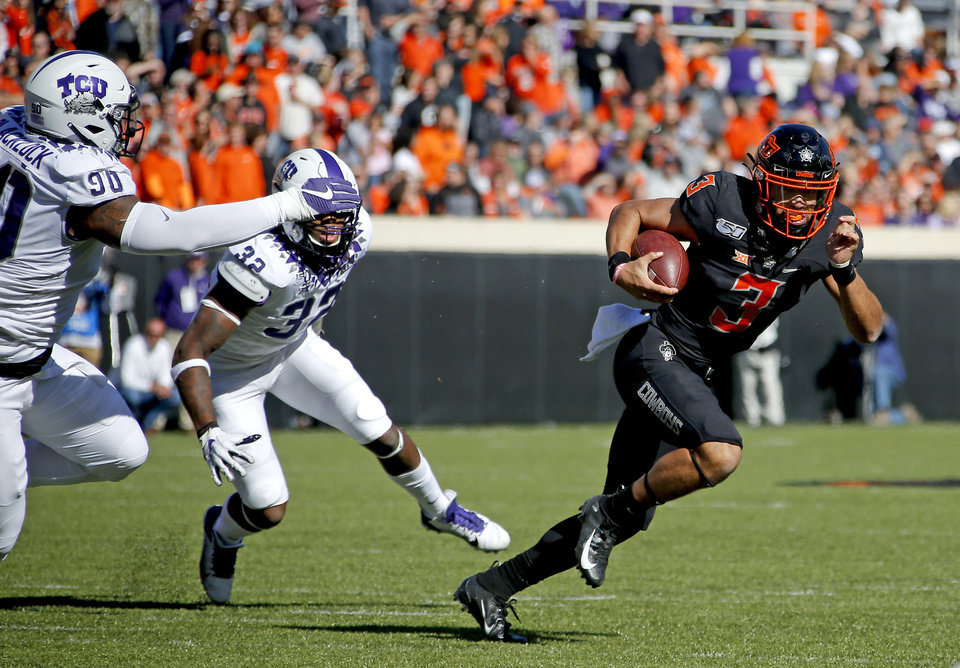 Photo - Oklahoma State's Spencer Sanders (3) scrambles as TCU's Ross Blacklock (90) and Ochaun Mathis (32) defend in the first quarter during the college football game between the Oklahoma State University Cowboys and the TCU Horned Frogs at Boone Pickens Stadium in Stillwater, Okla.,  Saturday, Nov. 2, 2019. [Sarah Phipps/The Oklahoman]