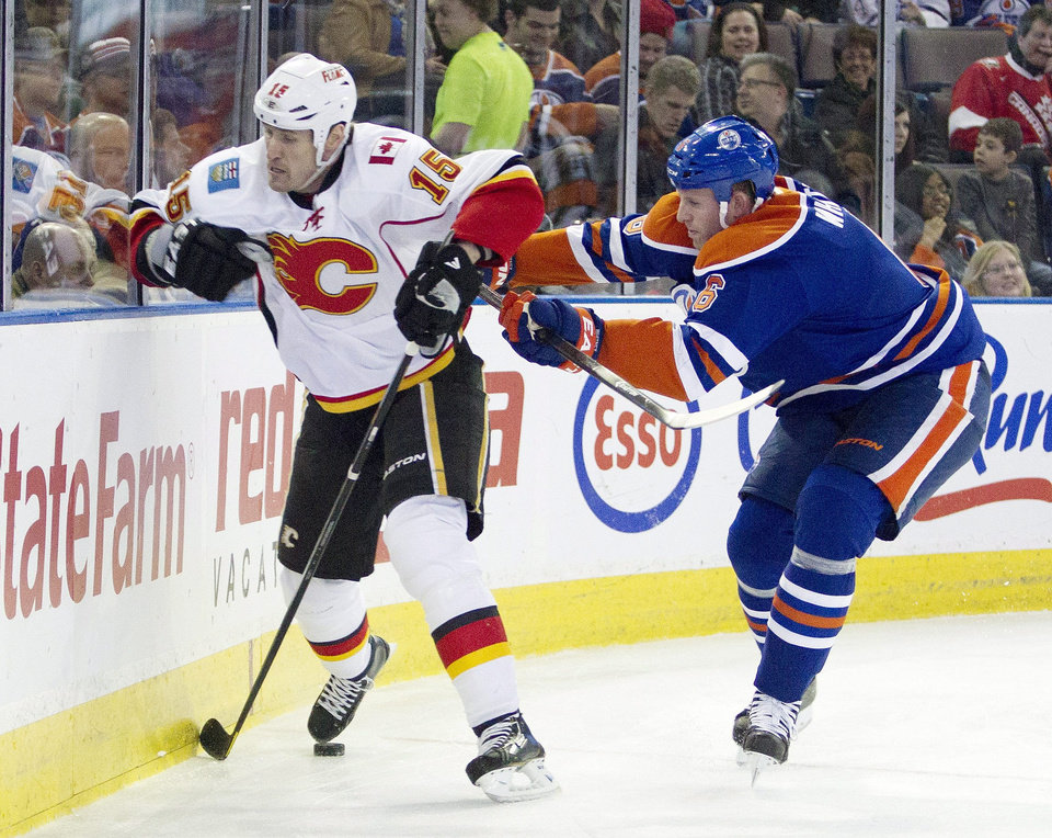 Photo - Calgary Flames Brian McGrattan (16) is checked by Edmonton Oilers Ryan Whitney (6) during first period NHL hockey action in Edmonton, Alberta, on Monday April 1, 2013.  (AP Photo/The Canadian Press, Jason Franson)