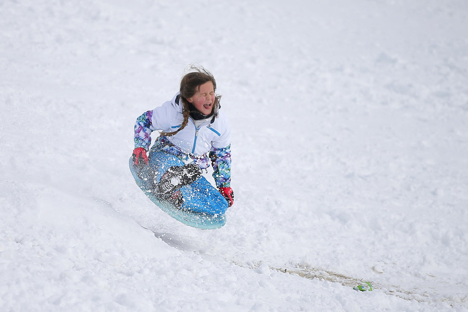 Photo - Harper Brown, 8, flies through the air while sledding down a hill along W Hefner Road in Oklahoma City after a winter storm dropped another layer of snow in Oklahoma City, Wednesday, Feb. 17, 2021. [Bryan Terry/The Oklahoman]