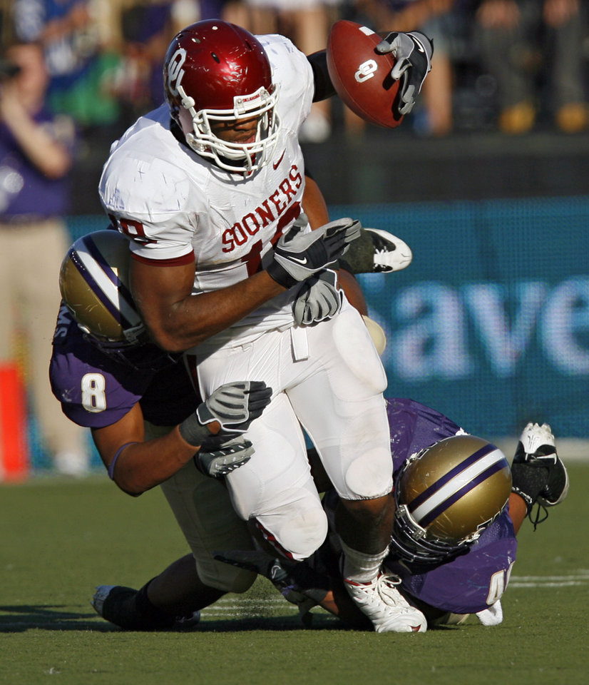 Photo - Oklahoma's Jermaine Gresham (18) is tackled by Washington's Nate Williams (8) and Mason Foster (40) during the first half of the college football game between the University of Oklahoma Sooners (OU) and the University of Washington Huskies (UW) at Husky Stadium on Saturday, Sep. 13, 2008, in Seattle, Wash. 
