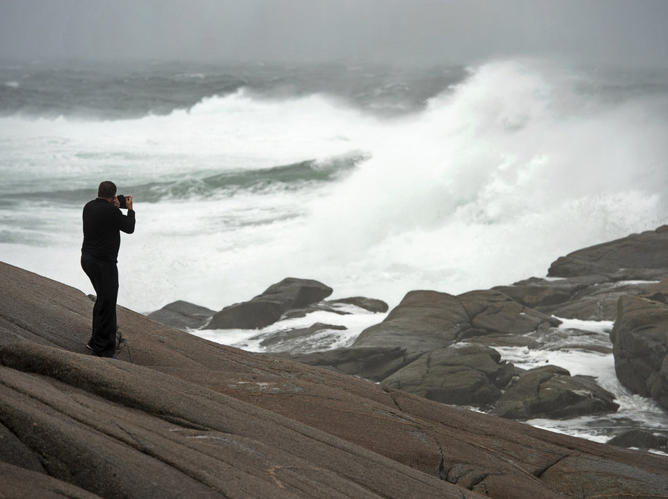 Photo - Photographer Gary Brinton braves the elements on the rocks at Peggy's Cove, Nova Scotia, as residents begin to feel the effects of tropical storm Arthur on Saturday, July 5, 2014. Thousands of homes and businesses were without power as heavy rains and high winds buffeted the region.(AP Photo/The Canadian Press, Andrew Vaughan)
