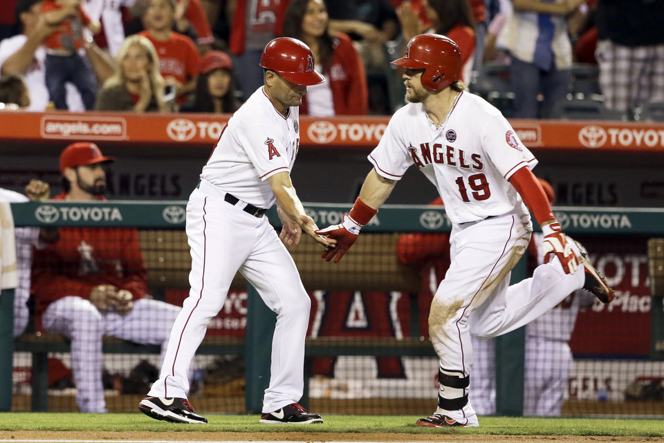 Photo - Los Angeles Angels' Collin Cowgill, right, is congratulated by coach Dino Ebel while rounding the bases on a solo home run against the Seattle Mariners in the fourth inning of a baseball game in Anaheim, Calif., Saturday, Sept. 21, 2013. (AP Photo/Reed Saxon)