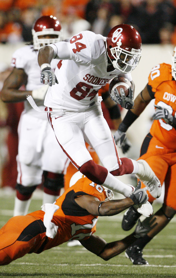 OSU's Perrish Cox hits the foot of a leaping Quentin Cheney and causes him to fall during the first half of the college football game between the University of Oklahoma Sooners (OU) and Oklahoma State University Cowboys (OSU) at Boone Pickens Stadium on Saturday, Nov. 29, 2008, in Stillwater, Okla. STAFF PHOTO BY NATE BILLINGS