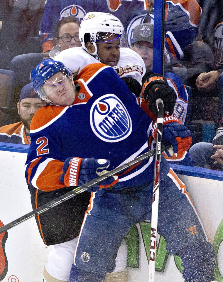 Photo - Anaheim Ducks Devante Smith-Pelly, rear, checks Edmonton Oilers Jeff Petry (2) during second period NHL hockey action in Edmonton,  Alberta, on Sunday April 6, 2014. (AP Photo/The Canadian Press, Jason Franson)