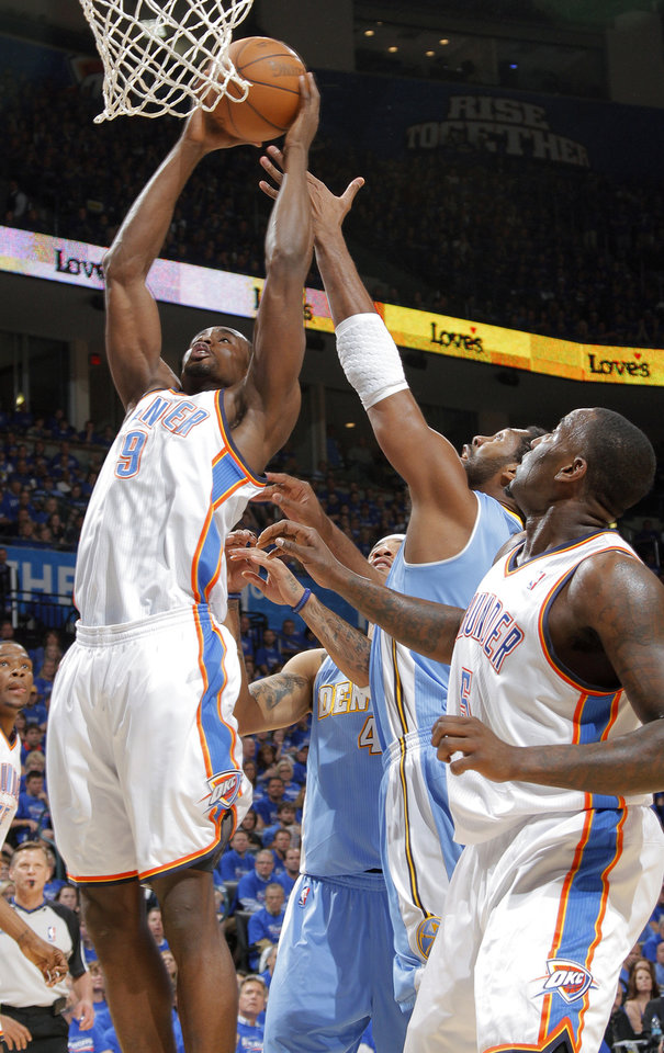 Photo - Oklahoma City's Serge Ibaka (9) battles under the basket with Denver's Nene (31) during the first round NBA playoff game between the Oklahoma City Thunder and the Denver Nuggets on Sunday, April 17, 2011, in Oklahoma City, Okla. Photo by Chris Landsberger, The Oklahoman
