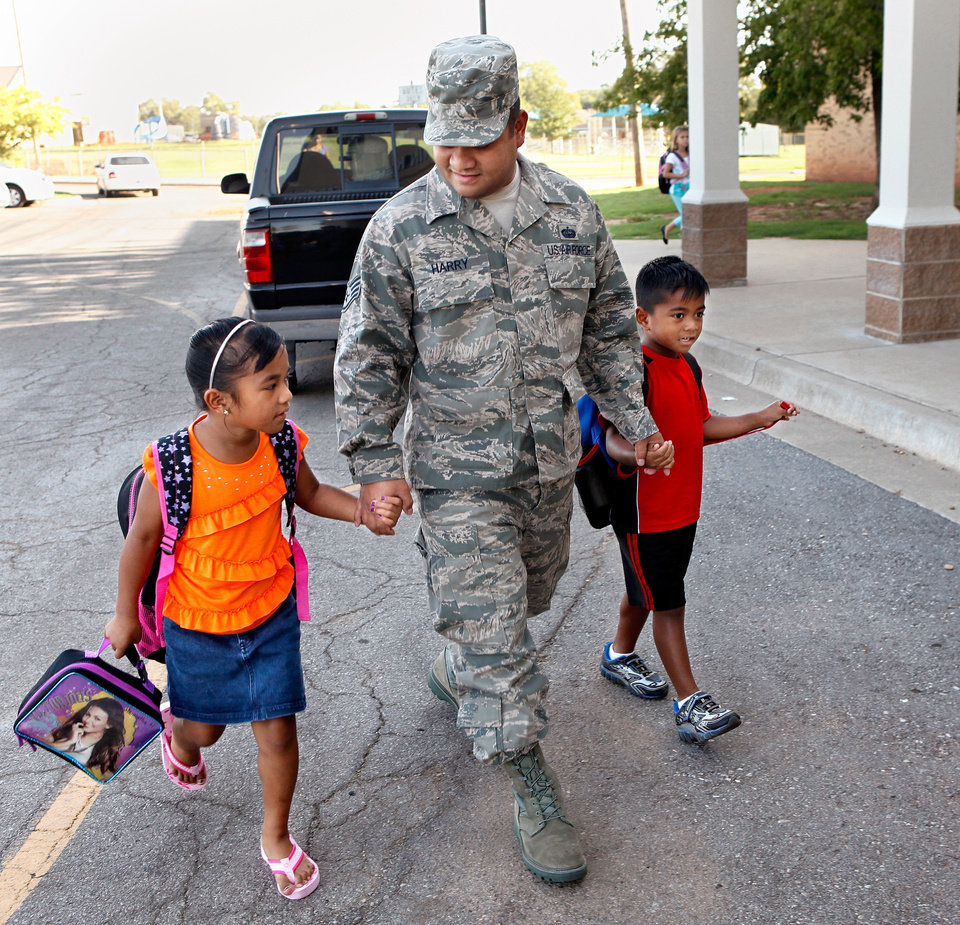 Photo - Ssgt. Wedler Harry, Jr. (USAF) walks his children into Tinker Elementary School on Friday, Aug. 19, 2011.  His son, Jared, is in the first grade. His daughter,  Maranatha, is in the 2nd grade.  Ssgt. Harry is assigned to HQ-APFSA in the Headquarters Building on Tinker Air Force Base.    by Jim Beckel, The Oklahoman.  ORG XMIT: KOD