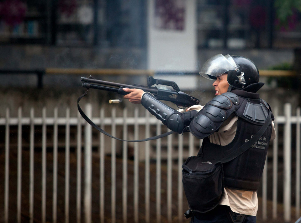 Photo - A Bolivarian National Police officer fires rubber bullets at demonstrators after clashes broke out at an at anti-government protest in Caracas, Venezuela, Thursday, May 8, 2014. Demonstrators took to the streets after a pre-dawn raid by security forces that broke up four camps maintained by student protesters and arrested more than 200 people. The tent cities were installed more than a month ago in front of the offices of the United Nations and in better-off neighborhoods in the capital to protest against President Nicolas Maduro's socialist government. (AP Photo/Alejandro Cegarra)