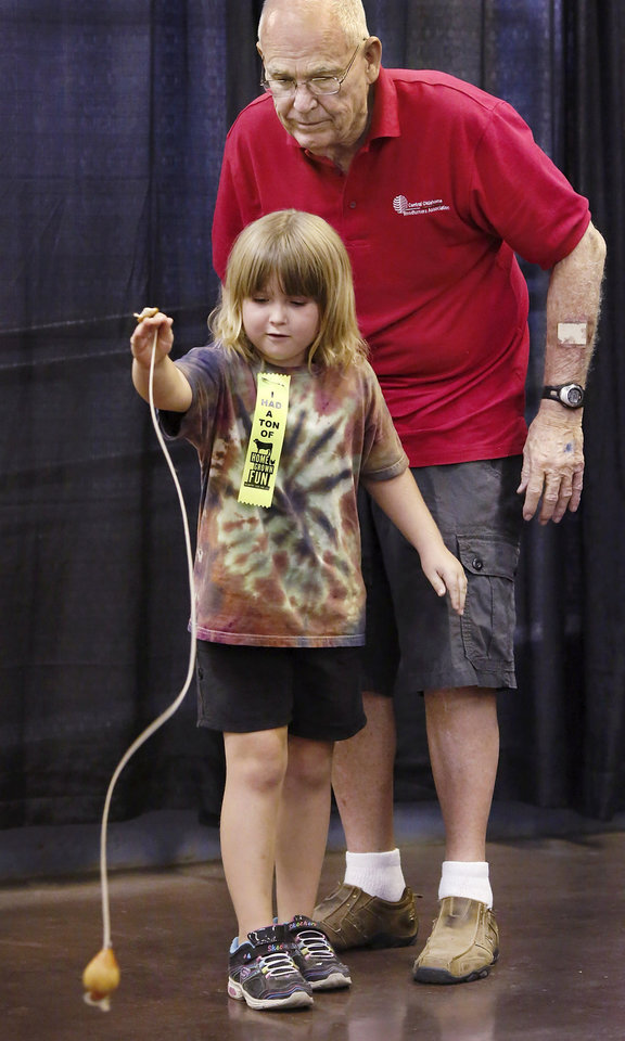 Photo - Bob Jarrett of Norman teaches Colleen Sommerfeld (cq), 7, of Lawton, to make a wooden top spin after releasing it from its string. Jarrett was among several members of the Central Woodturners  Association who at the group's booth in the Creative Arts Building at the Oklahoma State Fair on Saturday, Sep. 22, 2012.  Jarrett said he and fellow woodturners enjoy making wooden tops and watching the delight on children's faces when they master the release technique. The wooden top Jarrett uses here is the same one he played with as a small boy. Today was Sommerfeld's first time to throw a top and it was her first visit to the state fair. Photo by Jim Beckel, The Oklahoman.