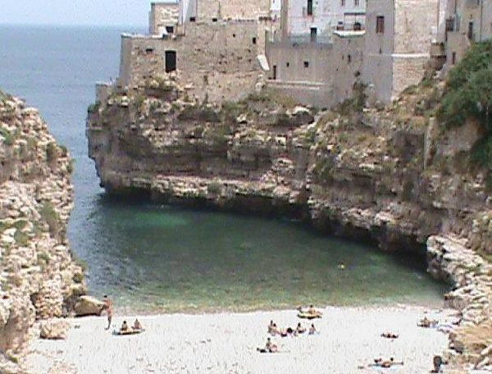 Photo - Residents of Polignano a Mare on the southeast Italian coast can often be seen swimming out to sea or enjoying the small white-sand beach. Homes also have been carved into the nearby hills. PHOTO BY JOE HIGHT, THE OKLAHOMAN.