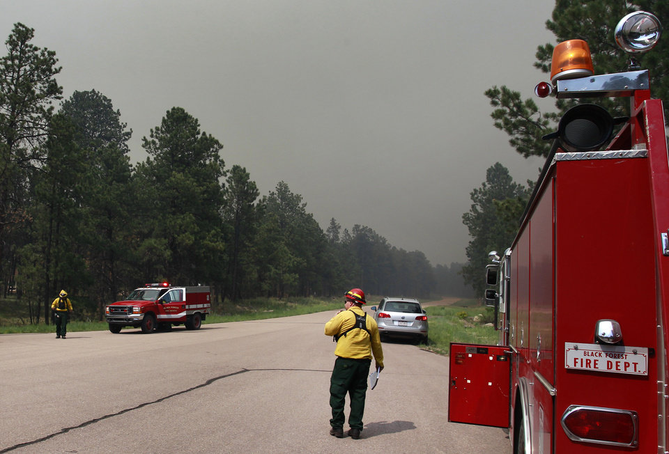 Photo - Black Forest Fire Dept. officers examine an evacuated neighborhood, prepping the area for encroachment of the wildfire in the Black Forest area north of Colorado Springs, Colo., on Wednesday, June 12, 2013. The number of houses destroyed by the Black Forest fire could grow to around 100, and authorities fear it's possible that some people who stayed behind might have died. (AP Photo/Brennan Linsley)