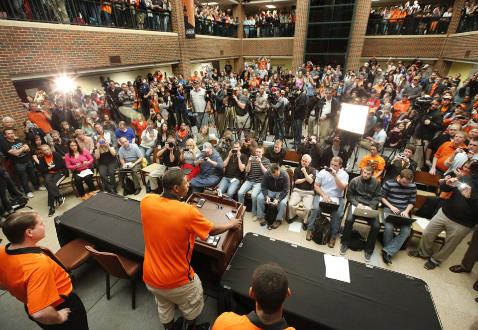 Photo - Marcus Smart speaks to fellow OSU students. Coach Travis Ford is at lower left. OSU basketball players Le'Bryan Nash, Markel Brown and Marcus Smart delighted  fans when they announced at a noontime press conference they intend to return for another season as members of the Cowboys basketball team. Cheering fans lined all levels in the Student Union atrium Wednesday, April 17, 2013.    by Jim Beckel, The Oklahoman.