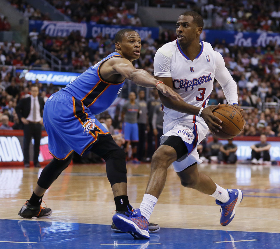 Photo - Clippers guard Chris Paul, right, drives past Thunder guard Russell Westbrook during the first half Wednesday in Los Angeles.                    AP Photo