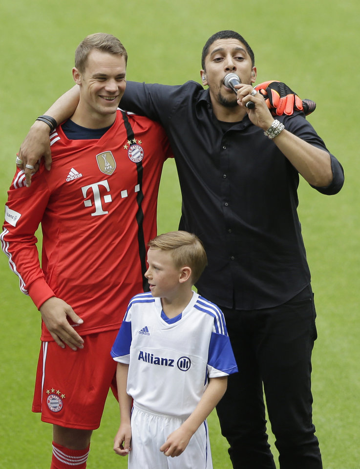 Photo - Singer Andreas Bourani, right, hugs Bayern Munich goalkeeper Manuel Neuer, as he performs during an official team presentation in the Allianz Arena stadium for the new German first division Bundesliga soccer season, in Munich, southern Germany, Saturday, Aug. 9, 2014. 65,000 spectators attended the event. (AP Photo/Matthias Schrader)