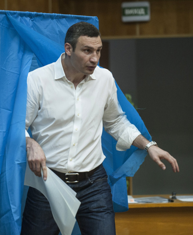 Photo - Vitali Klitschko Kiev's mayoral candidate, leaves a booth at a polling station during presidential and mayoral elections in Kiev, Ukraine, Sunday, May 25, 2014. Ukraine's critical presidential election got underway Sunday under the wary scrutiny of a world eager for stability in a country rocked by a deadly uprising in the east. (AP Photo/Evgeniy Maloletka)