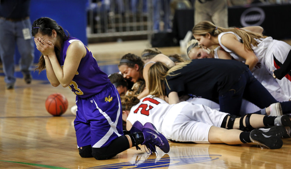 Photo - Anadarko junior Ashley Beatty drops to her knees, covers her face and sobs while a victorious Ft. Gibson team celebrates behind her at the end of the Class 4A State championship game between Ft. Gibson and Anadarko at Jim Norick Arena at State Fair Park  on Saturday, Mar. 15, 2014. Ft. Gibson came from behind much of the second half to win 50-47.  Photo by Jim Beckel, The Oklahoman