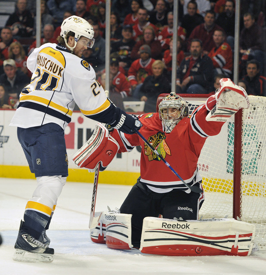 Photo - Nashville Predators' Matt Halischuk (24) tips the puck past the Chicago Blackhawks' Corey Crawford to score during the first period of an NHL hockey game on Friday, April 19, 2013, in Chicago. (AP Photo/Jim Prisching)