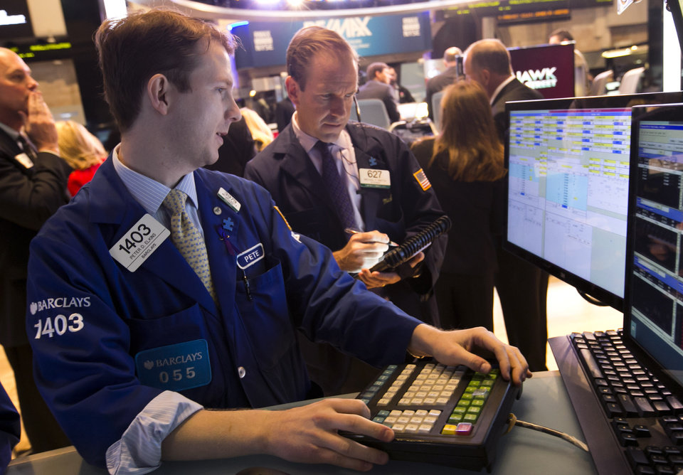 FILE - In this Tuesday, Nov. 12, 2013, file photo, specialist Peter Elkins, left, and trader Michael Smyth work on the floor of the New York Stock Exchange. Asian stock markets were boosted for a second day Friday Nov. 15, 2013 by the incoming Federal Reserve chief's support for continued massive stimulus to aid the U.S. economic recovery. Fragile growth prospects in Europe dampened markets there. (AP Photo/Richard Drew, File)