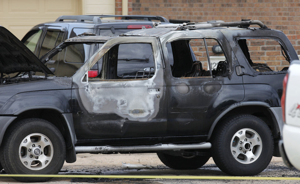Photo -  Oklahoma City police and arson investigators are shown at the scene of a vehicle fire Wednesday in Oklahoma City. Officials said a body was found inside the vehicle, but foul play is not suspected. Photo by Paul B. Southerland, The Oklahoman   PAUL B. SOUTHERLAND