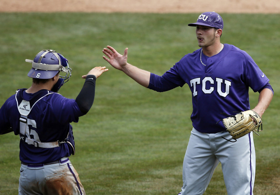 Photo - TCU's Riley Ferrell, right, high-fives catcher Kyle Bacak (6) after TCU defeated Baylor in a game in the Big 12 Conference NCAA college baseball tournament in Oklahoma City, Saturday, May 24, 2014. TCU won 4-1 and advances to the championship game on Sunday. (AP Photo/Sue Ogrocki)